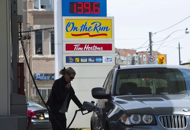 A woman pumps gas in Toronto on Tuesday, May 10,