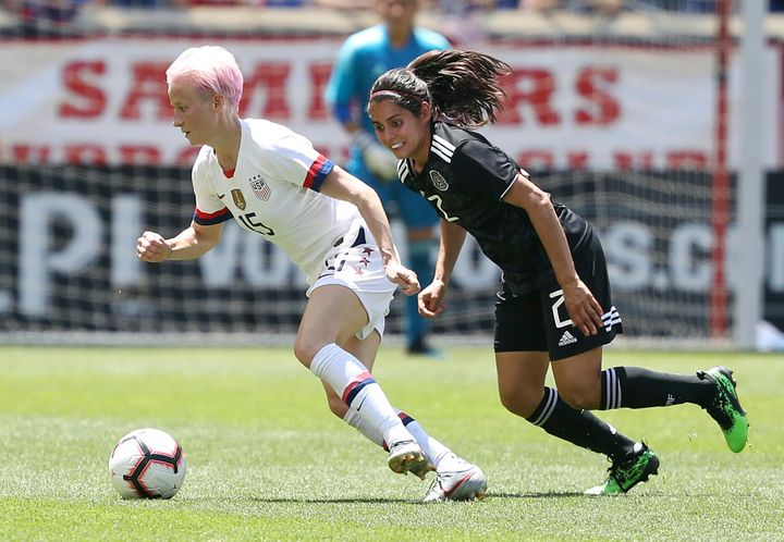 Megan Rapinoe, a forward player on the U.S. women's national team, dribbles the ball away from Mexico defender Kenti Robles i