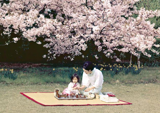 満開の桜の下で、ままごとをされる紀宮さま(黒田清子さん)と皇后さま=1973年4月、東京都港区の東宮御所(宮内庁提供)