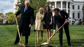 WASHINGTON, DC - APRIL 23: President Donald J. Trump and French President Emmanuel Macron plant a tree as first lady Melania Trump and Macron's wife Brigitte Macron watch on the South Lawn at the White House on Monday, April 23, 2018 in Washington, DC. (Photo by Jabin Botsford/The Washington Post via Getty Images)
