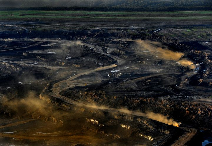 The oilsands open pit mine uses trucks that are 3 stories tall, weigh one million pounds, and cost 7 million dollars each, as shown here near Fort McMurray, Alta., June 20, 2012.
