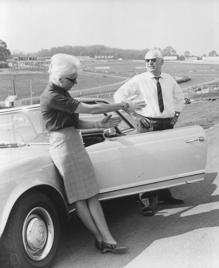 Badass racing driver Baroness Ewy von Korff-Rosqvist and Karl Kling standing next to a car as they discuss plans prior to a driving demonstration at Brand's Hatch, England, May 2, 1966.