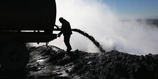 An worker unloads the dregs of oil refined into diesel fuel on November 14, 2015 near Derek, in Rojava,