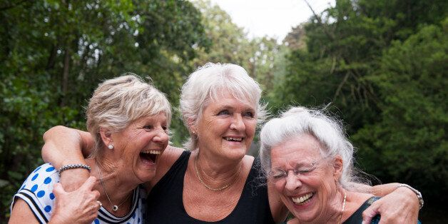 Three elderly women holding one another and laughing out loud, outdoors in a green environment on an overcast day.