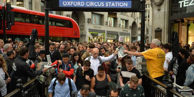 People queue at an entrance to Oxford Circus station, London, as workers try to get home before a strike...