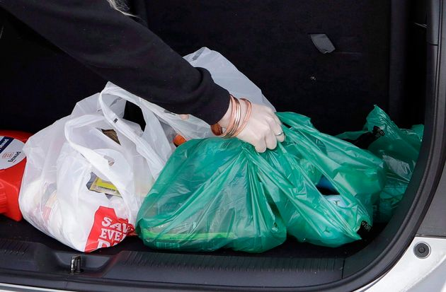 A shopper in New Zealand is seen here putting plastic bags filled with groceries in the trunk of her...