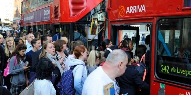 People queue for buses outside Liverpool Street Station, London, as commuters face travel misery trying...