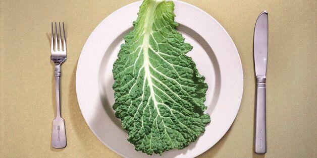 Single leaf of raw kale on ceramic dinner plate