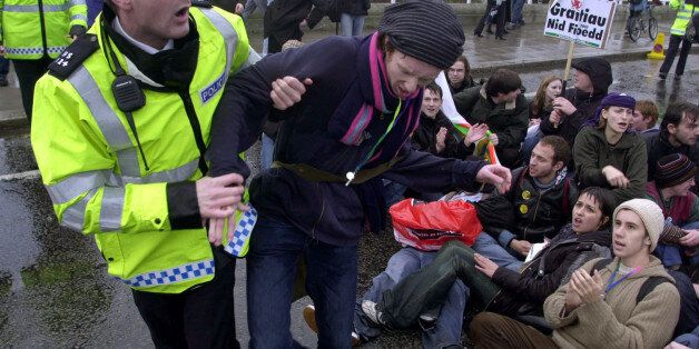 Matthew Walsh, 21, a student studying fine art at Pembroke College, Oxford, is pulled away by a police...