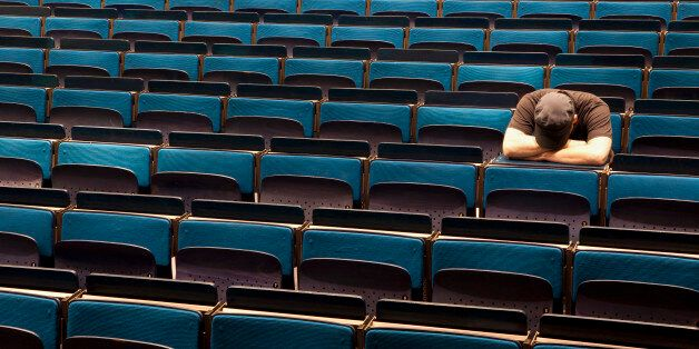 A man sitting in an auditorium with his head resting in his