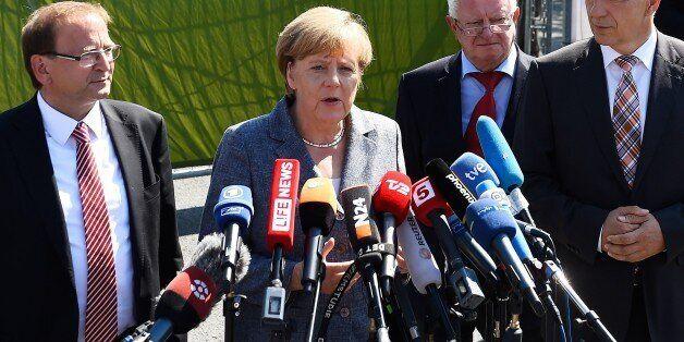 German Chancellor Angela Merkel (2nd L) makes a statement flanked by Heidenau's mayor Juergen Opitz (L),...