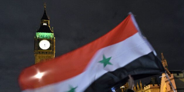 LONDON, ENGLAND - DECEMBER 01: Protesters hold up a Syrian flag as they take part in a Stop The War Coalition...