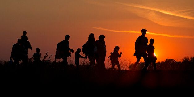 Refugees from the Middle East are silhouetted against the setting sun as they walk on railway tracks...