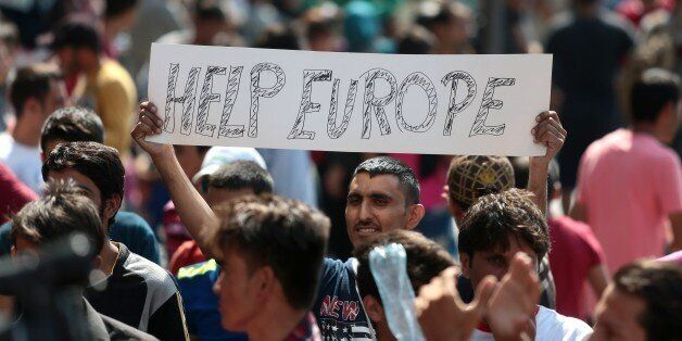 A man hold a placard reading 'Help Europe' as Syrian and Afgan refugees attend a protest rally to demand...