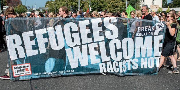 Protesters demonstrate with a banner 'Refugees welcome!' in Dresden, eastern Germany, Saturday, Aug....