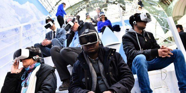Visitors test virtual reality headsets at the 'Solutions COP21' exhibition at the Grand Palais in Paris...