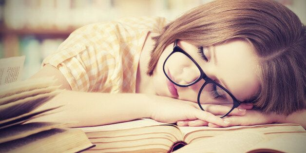 tired student girl with glasses sleeping on the books in the