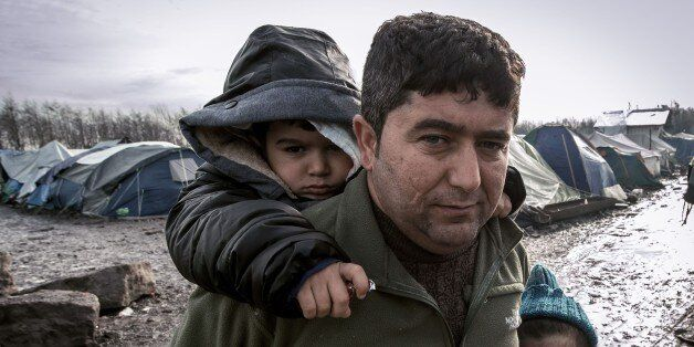 TOPSHOT - A man and his children from Iraq poses in the so-called 'Jungle' migrant camp in Gande-Synthe...