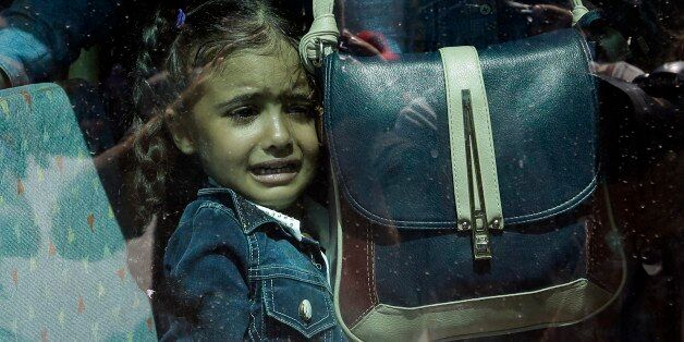 A girl cries as she waits on a bus which will transport her family to the metro station, after their...