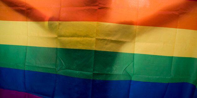 HANOI, VIETNAM - AUGUST 02: A vietnamese man dances as he holds a rainbow flag during the fourth gay...