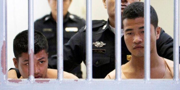 Myanmar migrants Win Zaw Htun, right, and Zaw Lin, left, both 22, are escorted by officials after their...