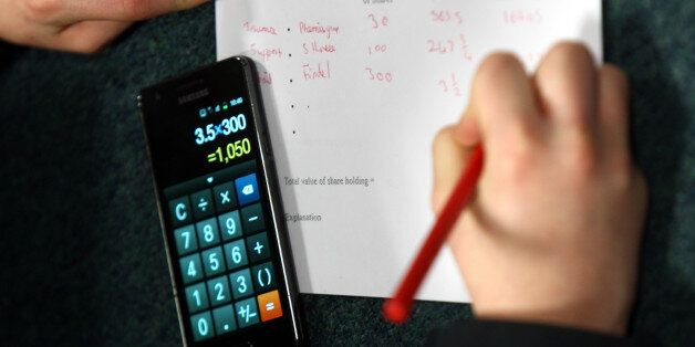 A generic stock picture of a pupil in an economics class using their mobile phone calculator to check...