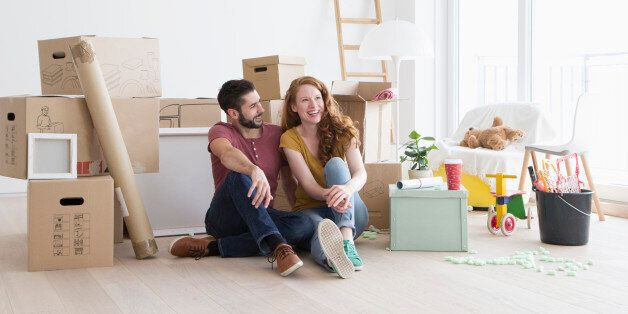 Young couple in new flat with cardboard boxes, sitting on