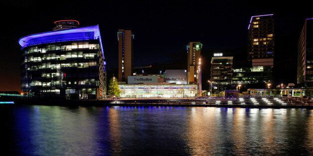The lights of offices and restaurants are reflected in the water at MediaCityUK in Salford Quays, Manchester,...