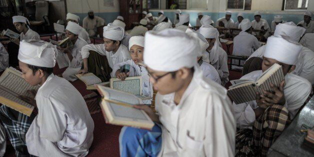 A Malaysian religious student (C) looks on as others read and memorise the Koran at a seminary during...