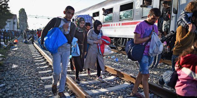 TOVARNIK, CROATIA - SEPTEMBER 18: People move past a train on the tracks as migrants remain at Tovarnik...