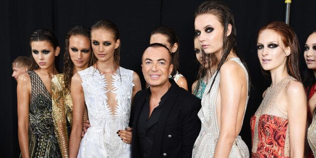 LONDON, ENGLAND - SEPTEMBER 19: Julien MacDonald (C) poses backstage with models at the Julien MacDonald...