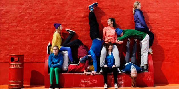 Young people sitting and lying on each other on a red
