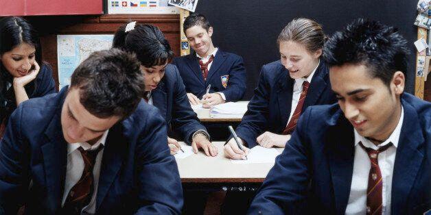 Teenage schoolchildren (14-16) writing in
