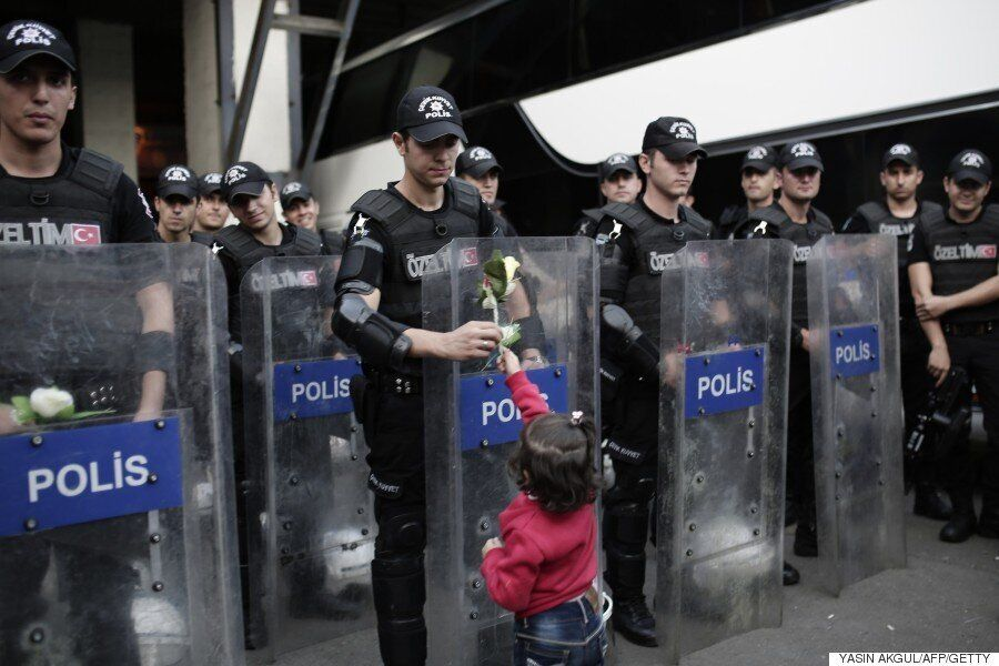 Refugee Crisis: Child Hands Flower To Turkish Riot Police Officer In Symbolic Gesture Of