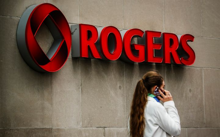 A woman speaks on her cell phone in front of a Rogers Communications sign before the company's annual general meeting in Toronto, April 22, 2014.