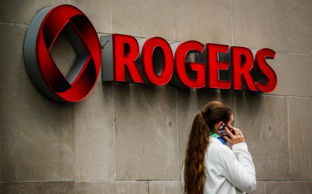 A woman speaks on her cell phone in front of a Rogers Communications sign before the company's annual...