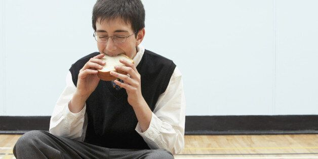 Boy (11-13) eating sandwich in school gymnasium, eyes
