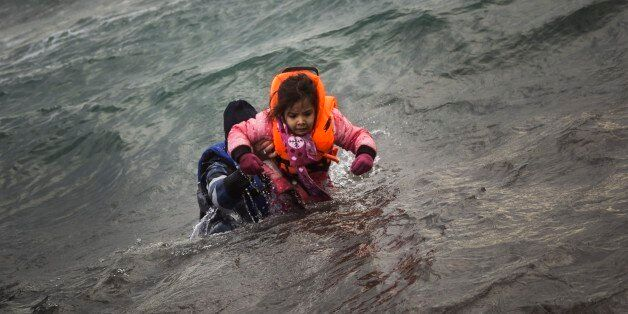 A man carries a child as they try to reach a shore after falling into the sea while disembarking from...