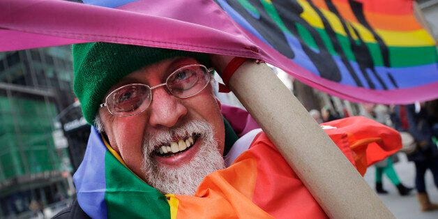 Artist Gilbert Baker, designer of the Rainbow Flag, is draped with the flag while holding a banner that