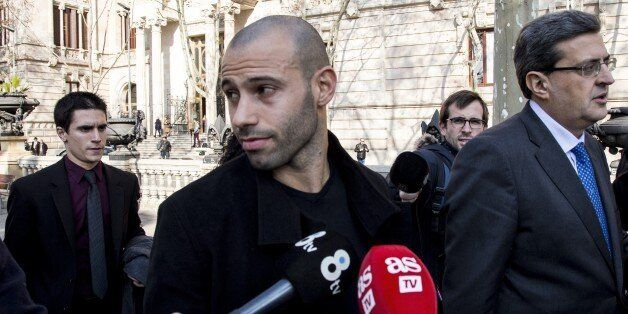 FC Barcelona's player Javier Mascherano (C) leaves the Barcelona's law court after his trial for unpaid...