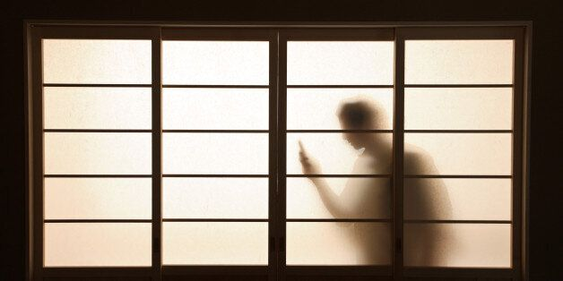 figure holding phone silhouetted behind
