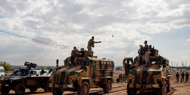 Turkish solders in military vehichles observe the street to the border with Syria in Suruc September...