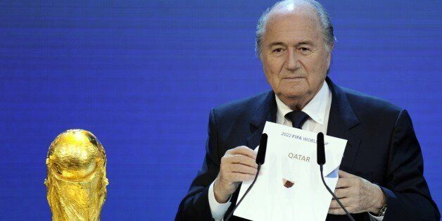 FIFA President Sepp Blatter holds up the name of Qatar during the official announcement of the 2022 World...