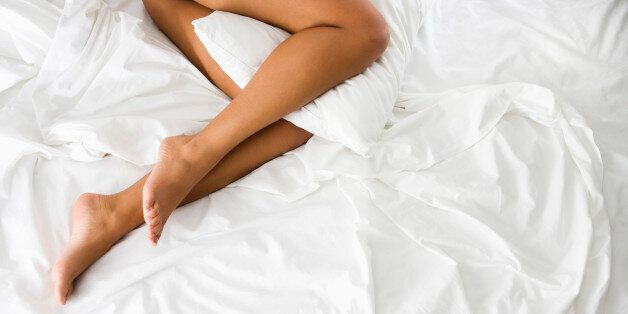 Above view of woman' || chr(39) || 's bare legs holding pillow between knees lying on bed with white