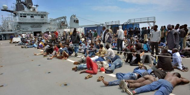 Royal Marines from HMS Bulwark help rescue migrants stranded on a boat, thirty miles off the Libyan