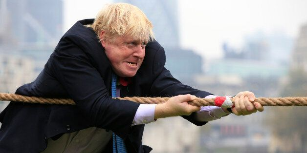 Mayor of London Boris Johnson takes part in a tug of war with personnel from the Royal Navy, the Army...
