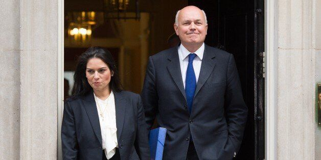 Employment Minister Priti Patel (L) and Work and Pensions Secretary Iain Duncan Smith leave the first...