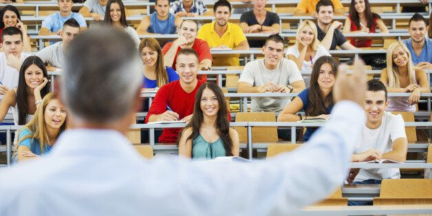 Rear view of a professor giving a lecture to a large group of students at the