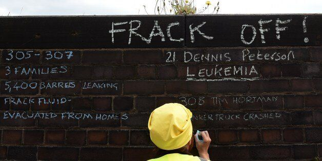 An anti-fracking demonstrator writes messages on a wall outside Lancashire County Hall in Preston, northwest...