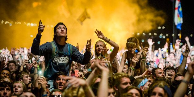 Fans dance on shoulders as they watch Kanye West performing on the Pyramid Stage at the Glastonbury Festival,...